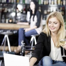 Beautiful young woman chatting with friends on her laptop while enjoying a glass of wine in a bar